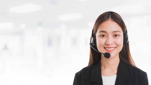 アジアの美しい笑顔の女性顧客の肖像画オフィススペースバナーの背景にテレフォンオペレーターをサポートします。 Premium写真