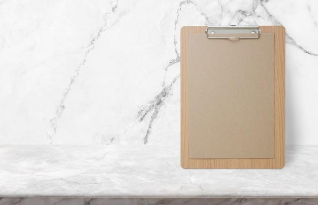 白い大理石の壁で石のテーブルの上に空白のエコ紙メモ帳 Premium写真