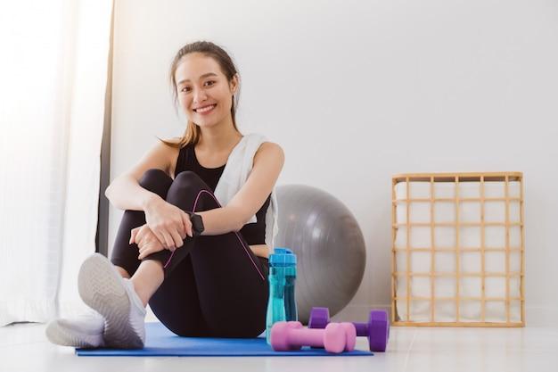アジアの女性がヨガをして自宅で運動後休んで Premium写真