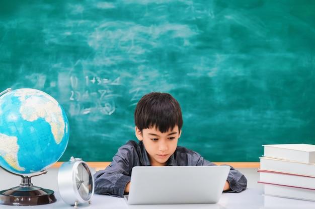 黒板にラップトップを使用してアジアの幸せな学校少年 Premium写真
