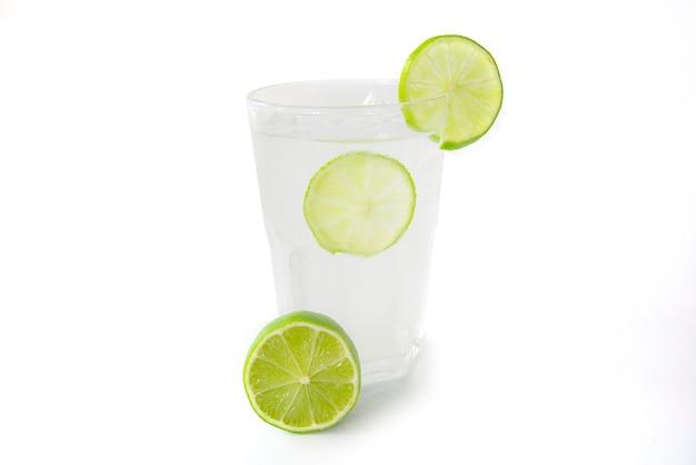 Свежий лимонный сок в прозрачном стакане, украшенный ломтиком ...