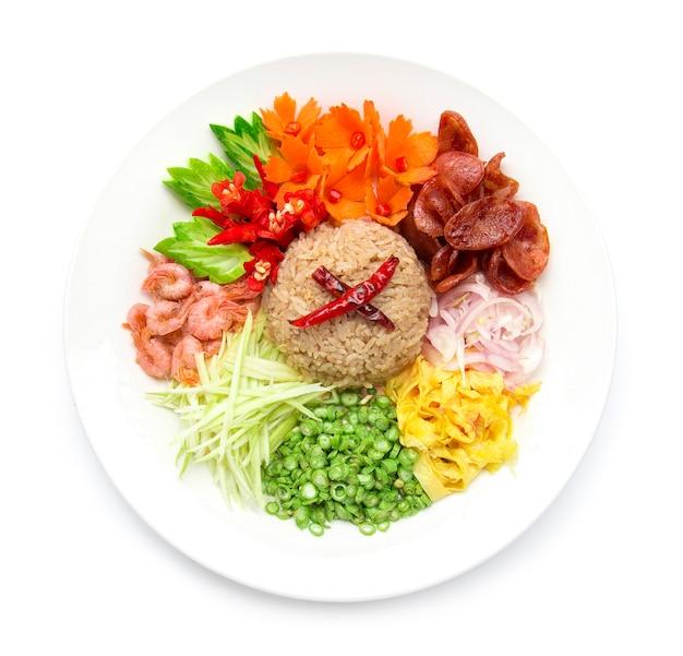 赤玉ねぎ、豆、マンゴー、目玉焼きのエビのペーストまたはライスミックススライスで味付けしたご飯、タイ料理スタイルのフュージョンは、白い背景で隔離された彫刻が施された野菜の上面と飾る Premium写真