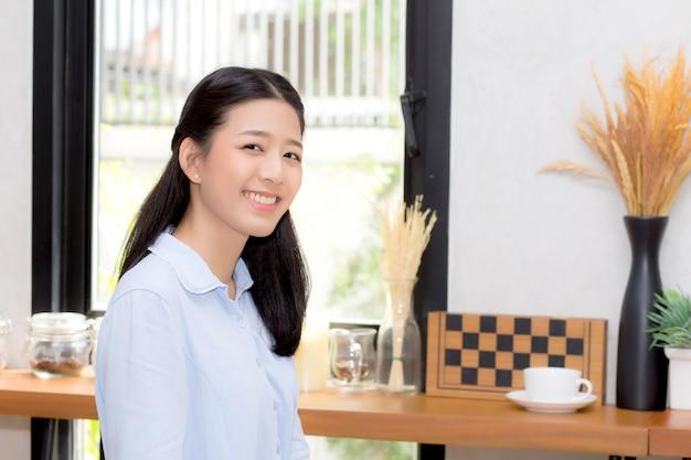カフェショップに座っている美しいアジアの女性の幸せの肖像 Premium写真
