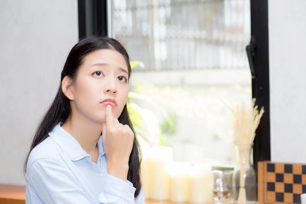 肖像画美しいアジアの女性の幸せとカフェショップで座って考える Premium写真