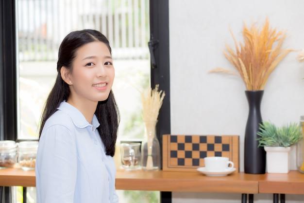 カフェショップに座っている美しいアジアの女性の肖像 Premium写真