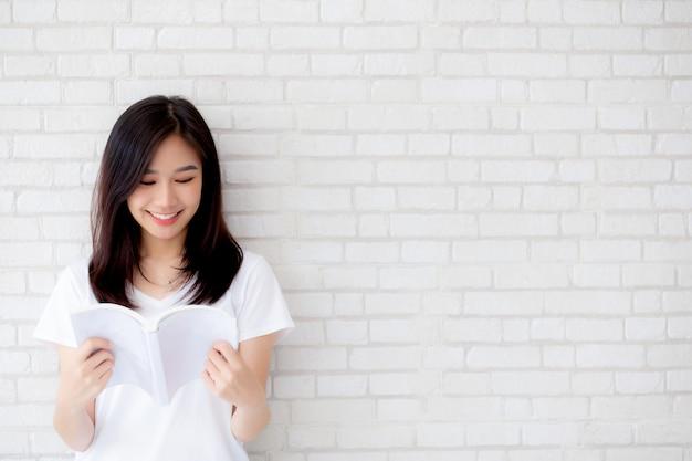 美しいアジアの女性は幸せな本を開く Premium写真