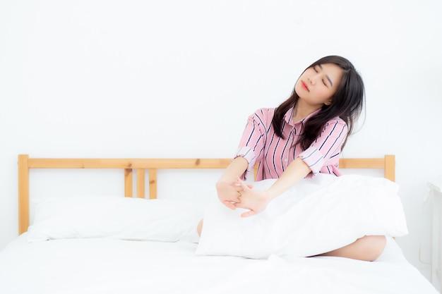 美しいアジアの女性はストレッチし、ベッドでリラックス Premium写真