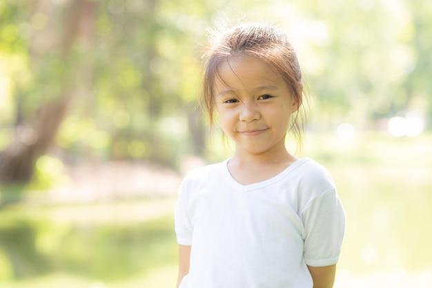 かわいいアジアの小さな女の子と子供の幸せと夏の公園で楽しいの肖像画顔 Premium写真