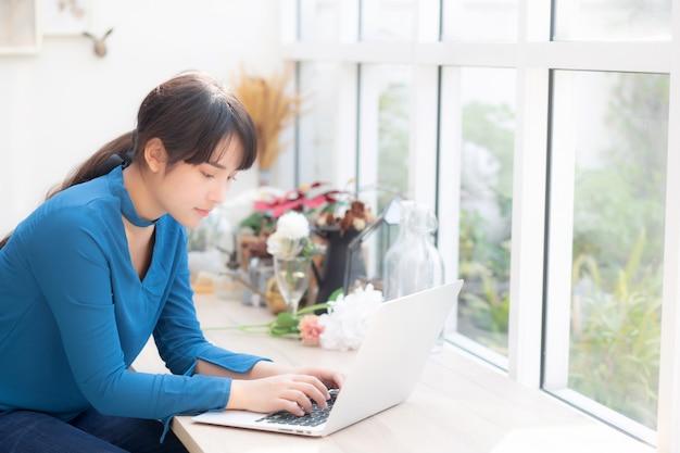 Красивый портрет азии молодая женщина работает онлайн на ноутбуке Premium Фотографии
