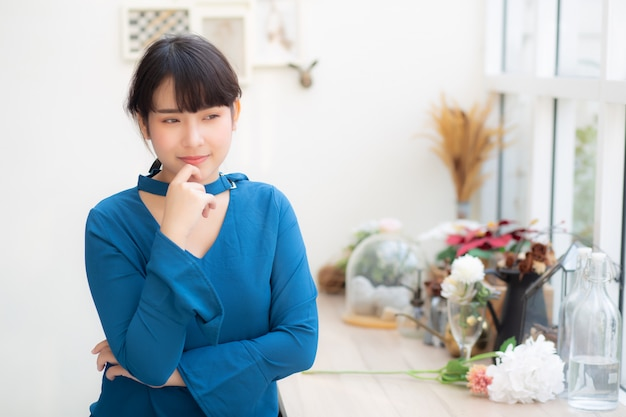 カフェに座って笑顔の美しい肖像若いアジア女性 Premium写真