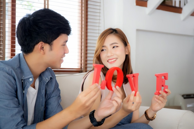 愛の言葉を一緒に保持してソファーに座っていた美しい肖像若いアジアカップル Premium写真