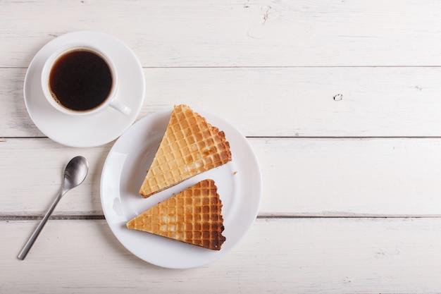 一杯のコーヒーと白い木製のテーブルの上皿に煮練乳とワッフルサンドイッチ。上面図 Premium写真