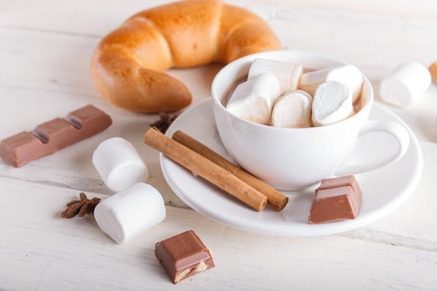 Чашка горячего шоколада с зефиром, круассаном и специями на белом деревянном фоне. Premium Фотографии