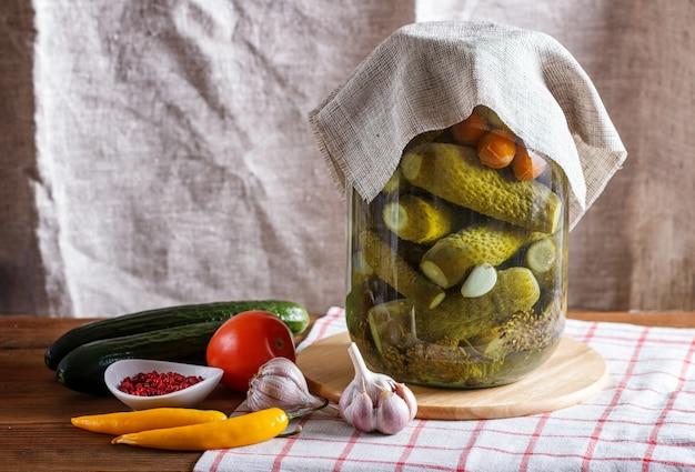 Маринованные огурцы и помидоры в стеклянной банке на льняной скатерти и деревянный стол. Premium Фотографии