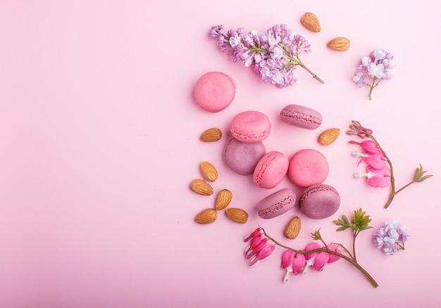 Фиолетовые и розовые пирожные с макарунами или макарунами с цветами сирени и кровоточащего сердца на пастельно-розовом. Premium Фотографии