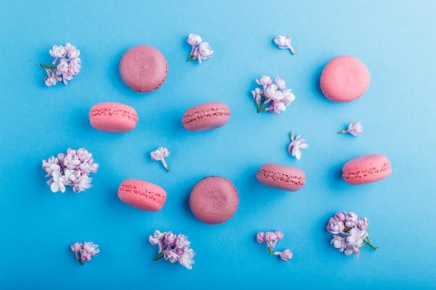 パステルブルーのライラック色の花と紫とピンクのマカロンまたはマカロンのケーキ。 Premium写真