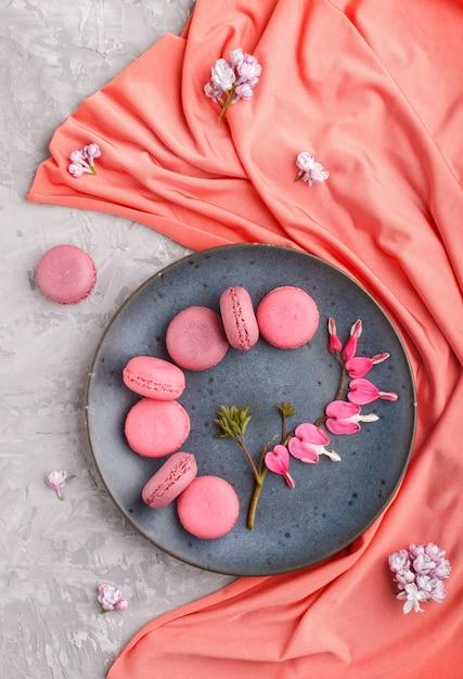 灰色のコンクリートの赤い繊維と青いセラミックプレートに紫とピンクのマカロンまたはマカロンケーキ。 Premium写真