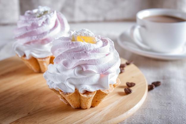 木の板にホイップエッグクリームのケーキ。 Premium写真