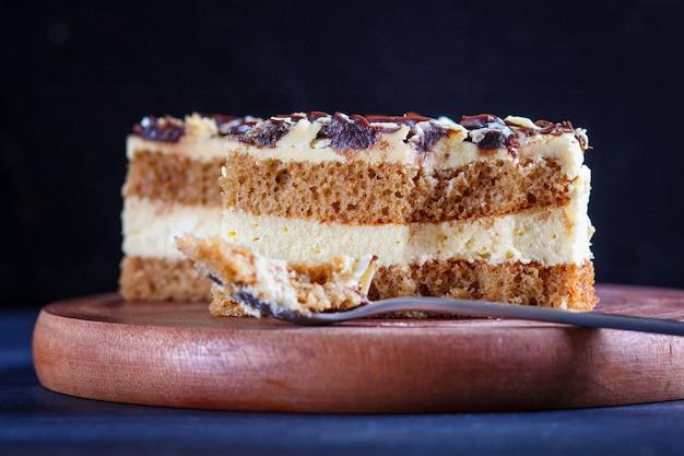 木製キッチンボード、黒いテーブルにスプーンで刈ったミルクとバタークリームのケーキ。 Premium写真