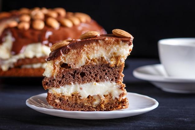 ミルククリーム、キャラメル、黒い木製のテーブルにアーモンドの自家製チョコレートケーキ。 Premium写真