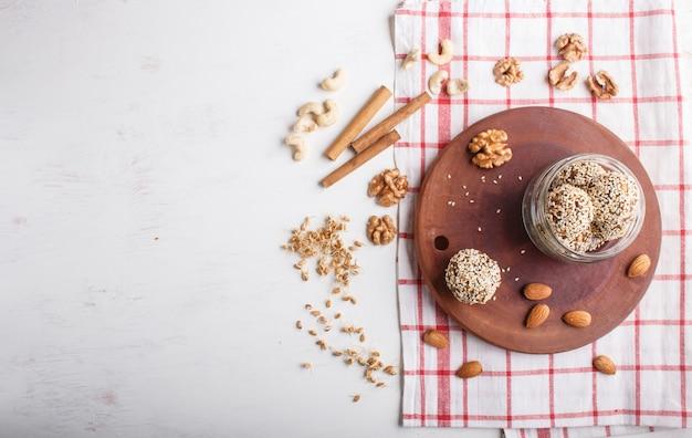 ガラス玉、アーモンド、ゴマ、カシューナッツ、クルミ、日付と発芽小麦のエネルギーボールケーキ、上面図。 Premium写真