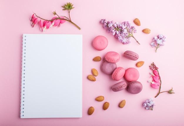 ノートブックとライラック、出血ハートの花と紫とピンクのマカロンまたはマカロンケーキ Premium写真