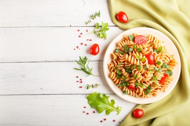フジッリパスタ、トマトソース、チェリートマト、レタス、ハーブ入り Premium写真