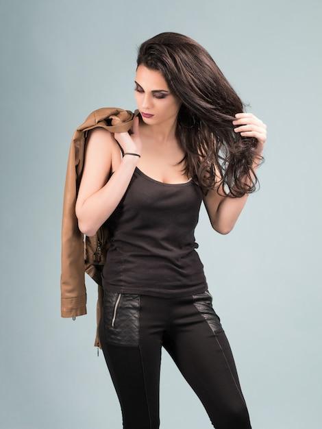 長い茶色の髪と革のジャケットの美しい少女の肖像画 Premium写真