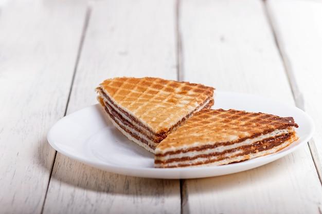 白い木製のテーブルの上のプレートに煮コンデンスミルクワッフルサンドイッチ Premium写真