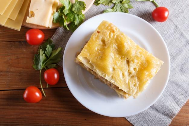 Лазанья с рубленым мясом и сыром на коричневой деревянной. Premium Фотографии