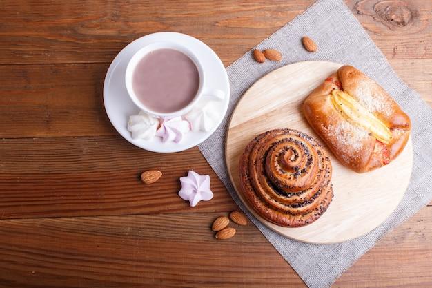 ホットチョコレートと茶色の木製の背景にパンのカップ。 Premium写真