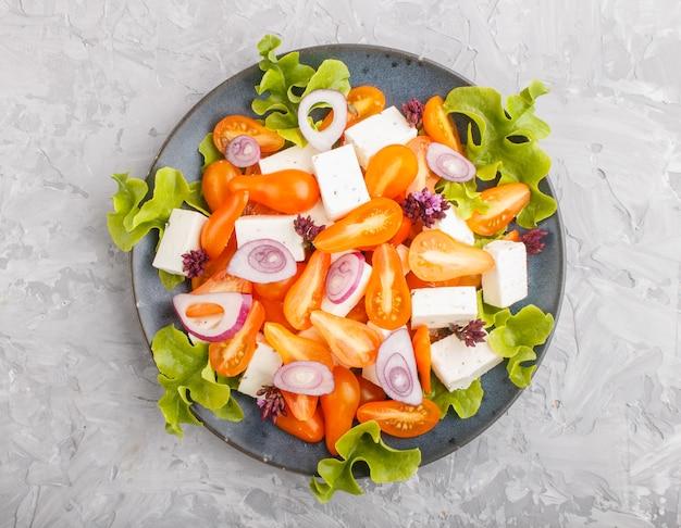 新鮮なブドウのトマト、フェタチーズ、レタス、タマネギのベジタリアンサラダ、トップビュー。 Premium写真