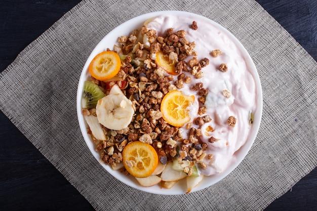 Вегетарианский салат из бананов, яблок, груш, кумкватов, киви с мюсли и йогурт на черном фоне деревянные. Premium Фотографии