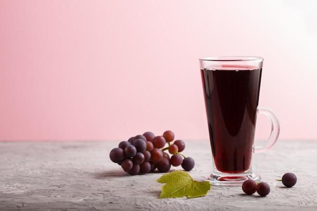 Стакан сока красного винограда на сером и розовом фоне. вид сбоку Premium Фотографии