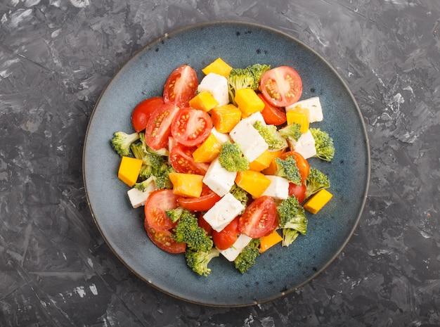 ブロッコリー、トマト、フェタチーズ、カボチャと青いセラミックプレートのベジタリアンサラダ Premium写真