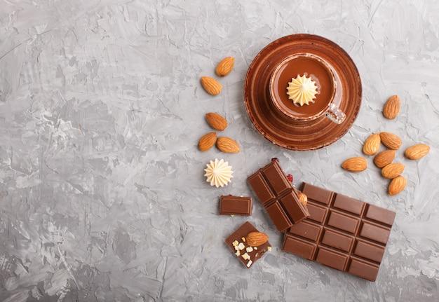 一杯のホットチョコレートと灰色のコンクリート背景にアーモンドとミルクチョコレートの部分 Premium写真
