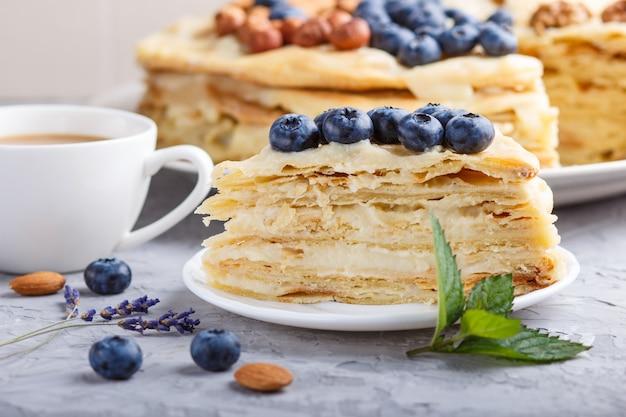 自家製の層状ナポレオンケーキとミルククリーム。ブルーベリー、アーモンド、クルミ、ヘーゼルナッツで飾られた Premium写真