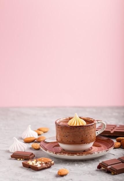 ホットチョコレートカップとグレーとピンクのアーモンド入りミルクチョコレート片。側面図、セレクティブフォーカス。 Premium写真