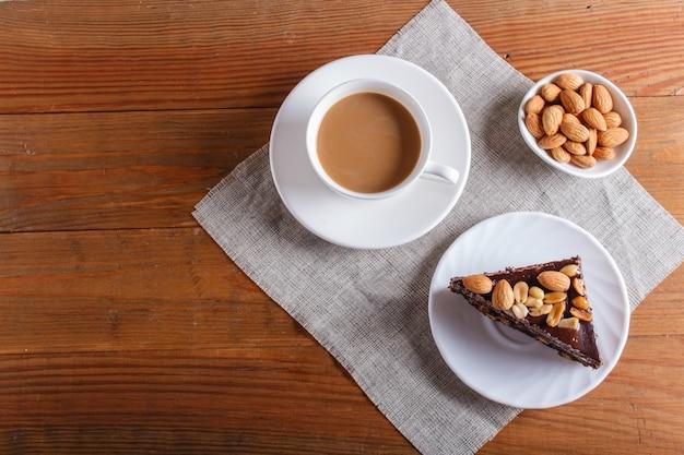 キャラメルピーナッツと茶色の木製の背景にアーモンドチョコレートケーキ Premium写真