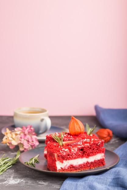黒とピンクの壁にコーヒーカップとミルククリームとイチゴの自家製の赤いベルベットのケーキ。側面図、選択と集中、コピースペース。 Premium写真