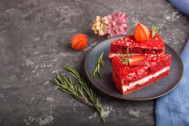 黒いコンクリートの表面にミルククリームとイチゴの自家製の赤いベルベットのケーキ。側面図、コピースペース。 Premium写真