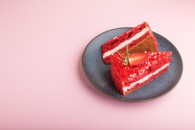 ミルククリームとピンクのパステル調の背景に分離された青いセラミックプレートにイチゴの自家製の赤いベルベットのケーキ。側面図、コピースペース。 Premium写真