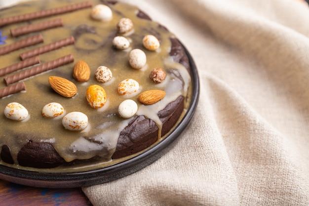 Домашний шоколадный брауни торт с карамельным кремом и миндаль с чашкой кофе на цветном деревянном фоне. Premium Фотографии