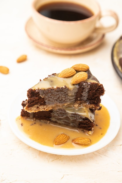 Кусочки торта шоколадный брауни с карамельным кремом и миндалем на белом фоне конкретных. Premium Фотографии