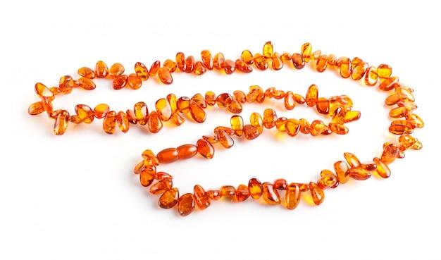 Оранжевые янтарные бусы на белом фоне Premium Фотографии