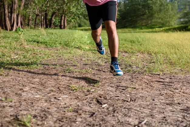 アジア人の男性が日没時に林道を走る Premium写真