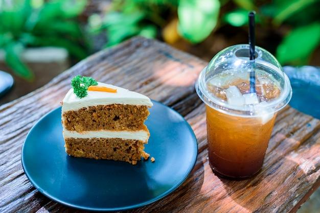 庭の木製テーブルの上のコーヒーとキャロットケーキ Premium写真