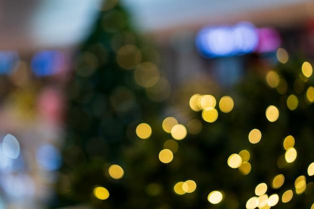 クリスマスの金色の光はパーティー、クリスマスツリーのキラキラとぼやけたライト背景コンセプトを祝います。 Premium写真