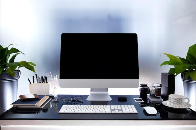 ガラステーブルの上の現代のコンピューターと職場、黒い画面、観葉植物と用品を模擬します。 Premium写真