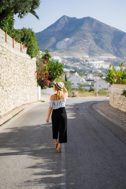 若い美しい女性が小さなヨーロッパの町の通りを通って歩きます。夏休み 無料写真